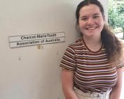 New Office Assistant Eleanor standing front of door with Charcot Marie Tooth Association Australia wording on the door